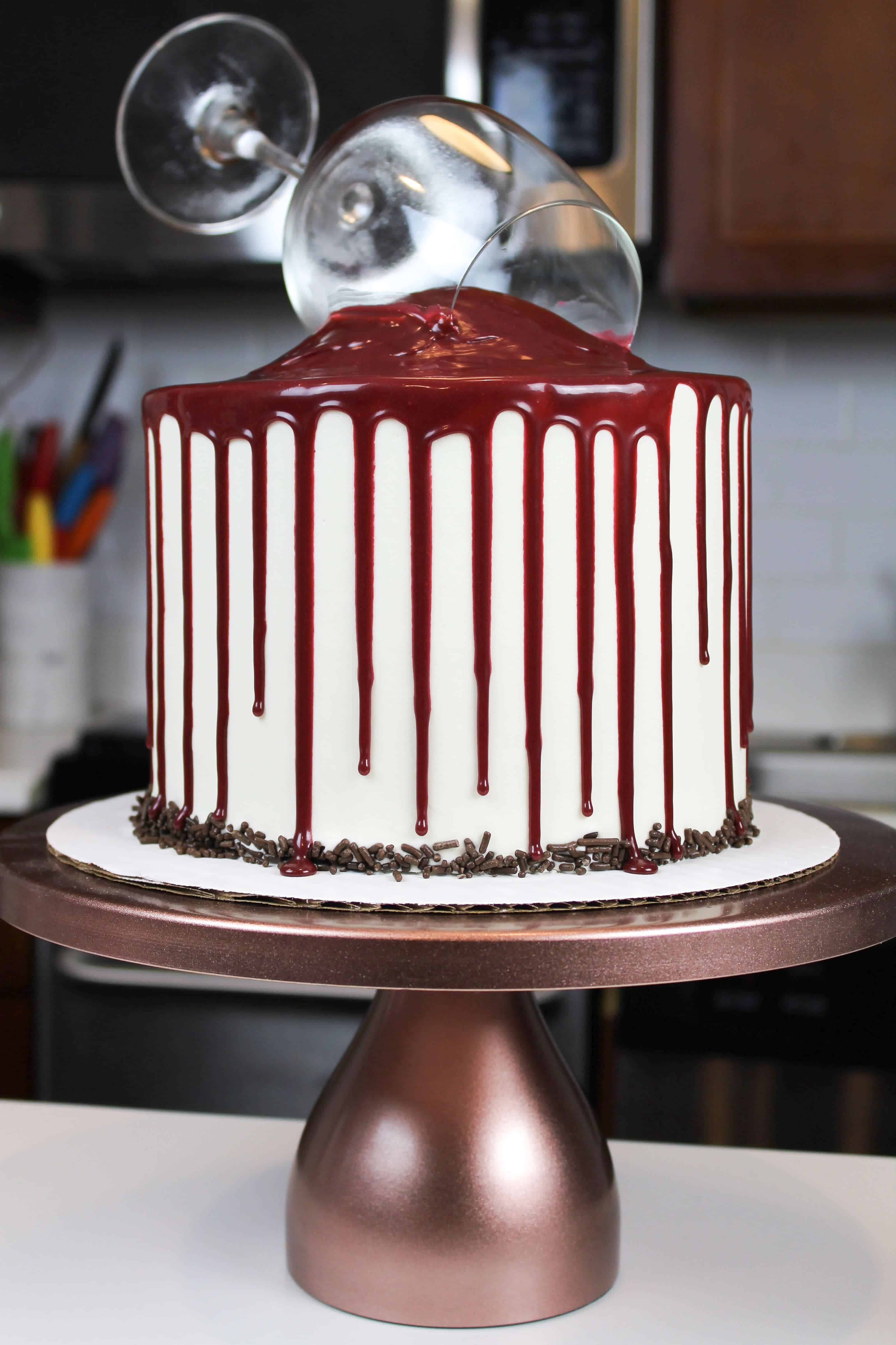 image of decorated red wine cake, with red wine drips and chocolate sprinkles around the base