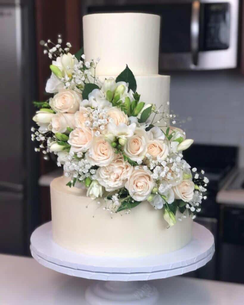 image of wedding cake with fresh white and green florals