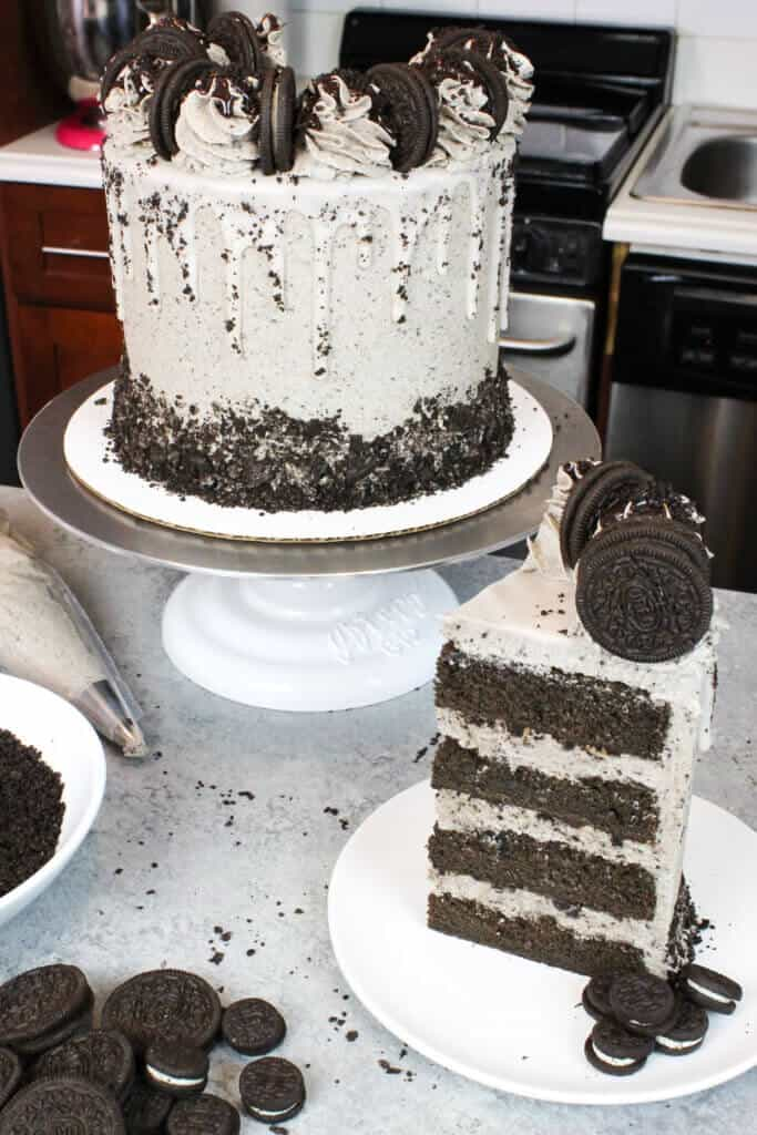 image of a chocolate oreo drip cake, with a white drip and oreo buttercream