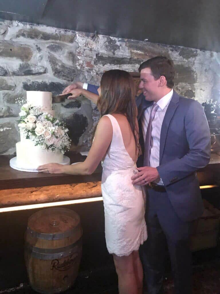 photo of chelsey white-frankola cutting into her wedding cake