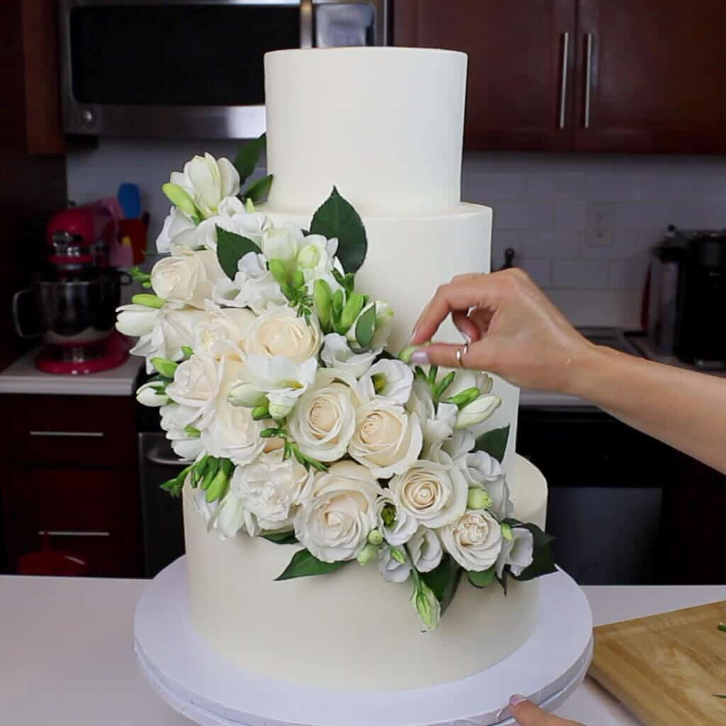 photo of 4 tier wedding cake decorated with fresh flowers