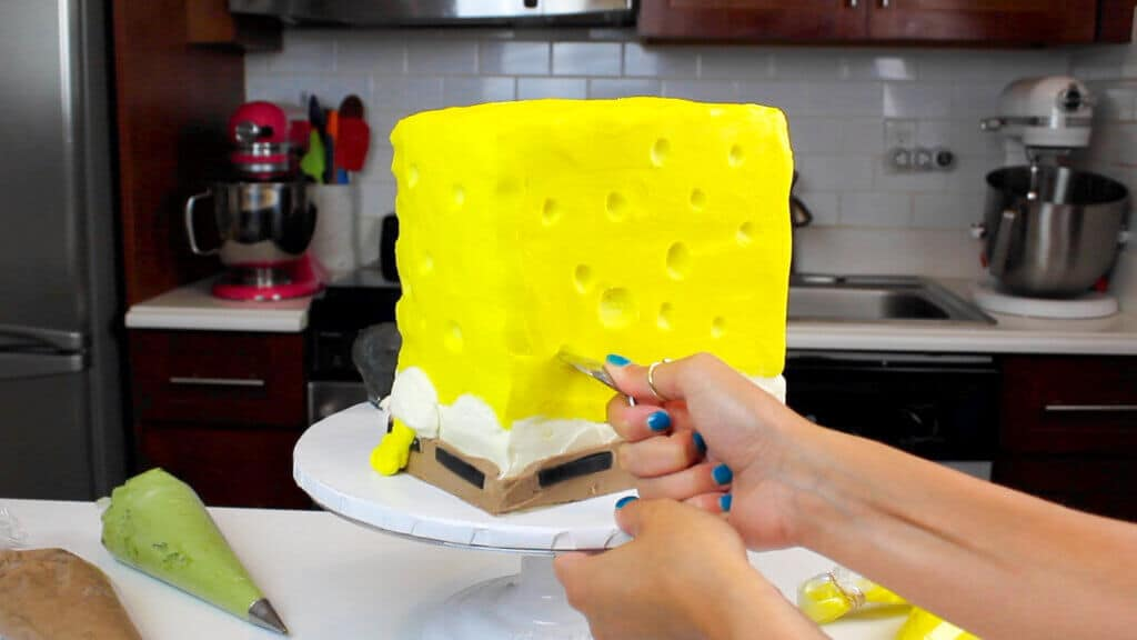 carving holes into spongebob cake with a small spoon