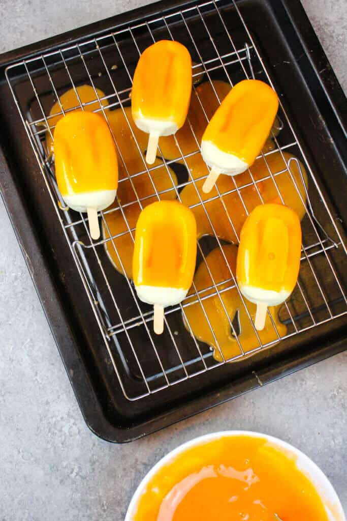 image of orange creamsicle cakesicles, covered in orange mirror glaze