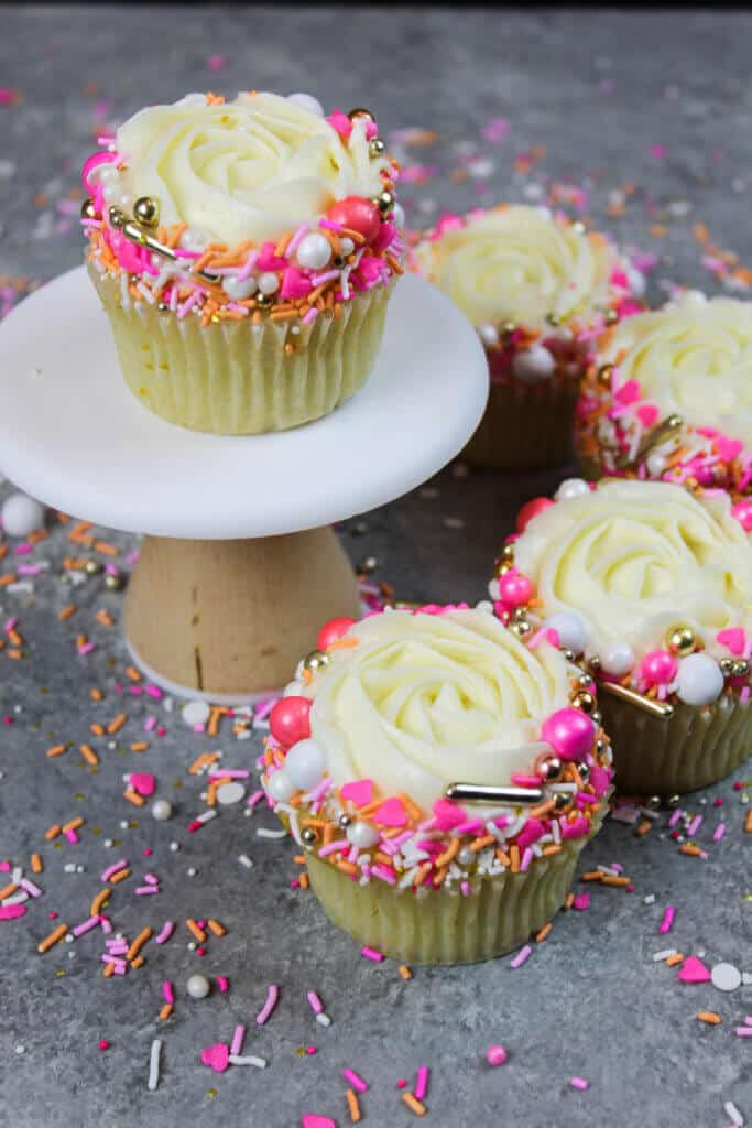image of unwrapped vanilla cupcake decorated with a pretty sprinkle blend