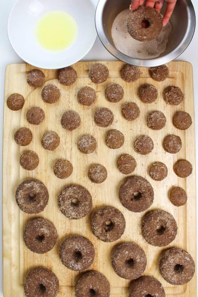 image of apple cider donuts being made from scratch and dunked in cinnamon sugar
