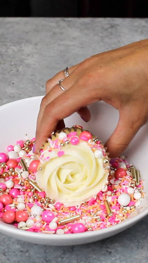 image of adding sprinkles to side of cupcake