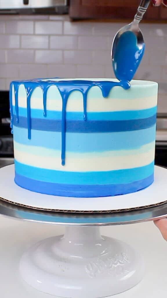 image of a blue colored drip being added to a striped blue cake
