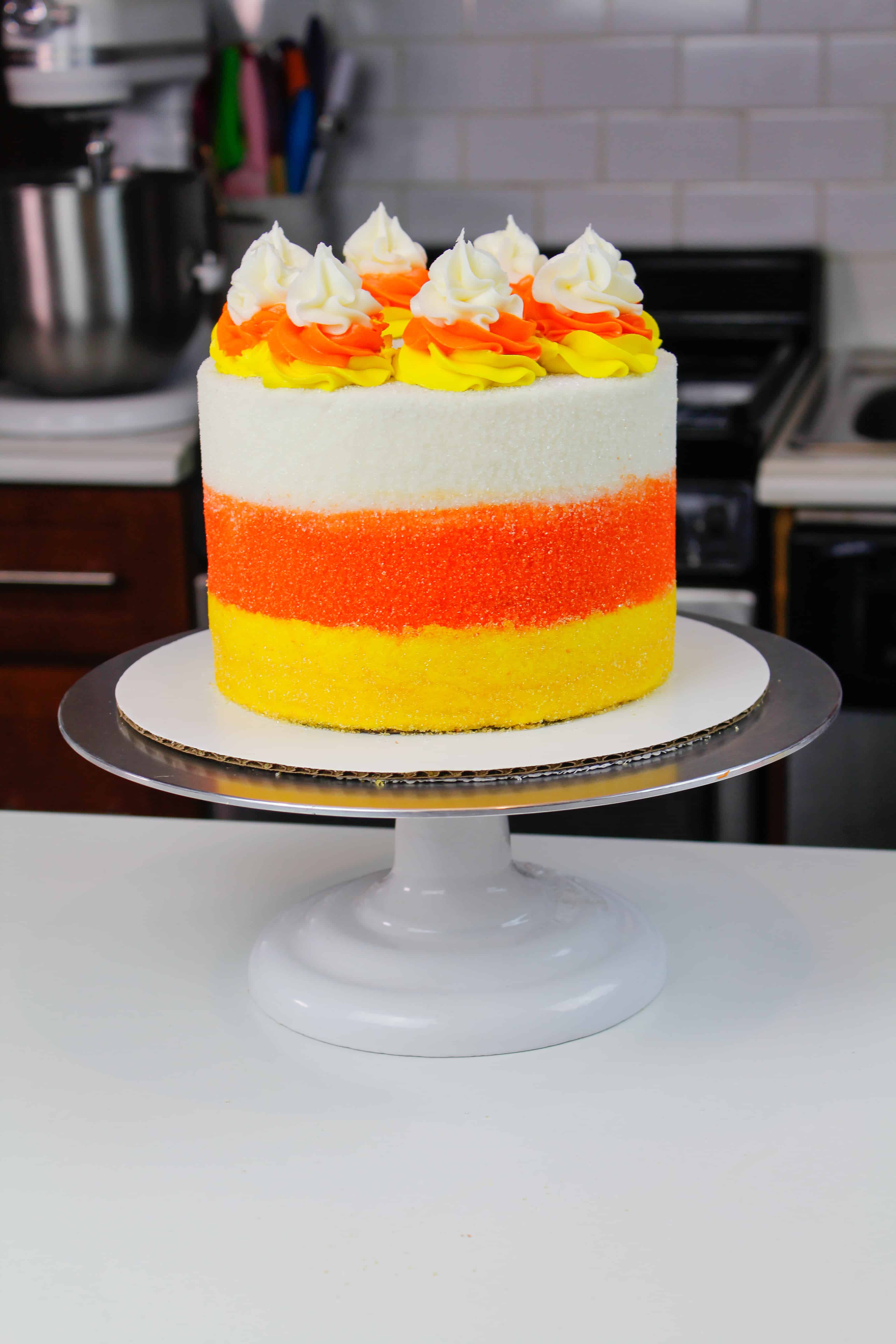 image of candy corn cake, frosted with yellow, orange, and white marshmallow buttercream swirls