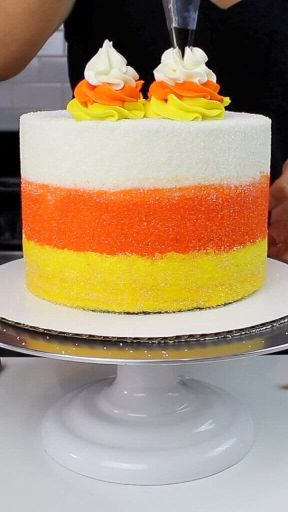 image of piping frosting on top of the cake with a wilton 1M frosting tip