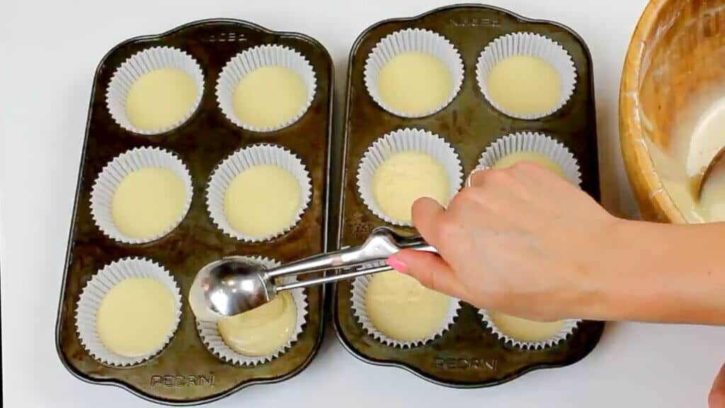 image of scooping vanilla cupcake batter into liners