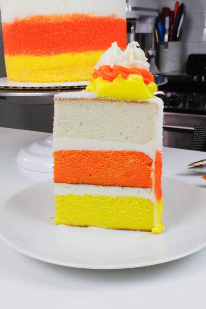 image of candy corn cake slice, with yellow, orange, and white cake layers