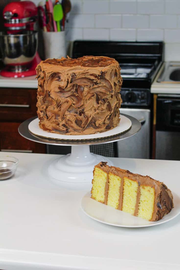 image of the best yellow cake recipe, sliced and frosted with chocolate buttercream