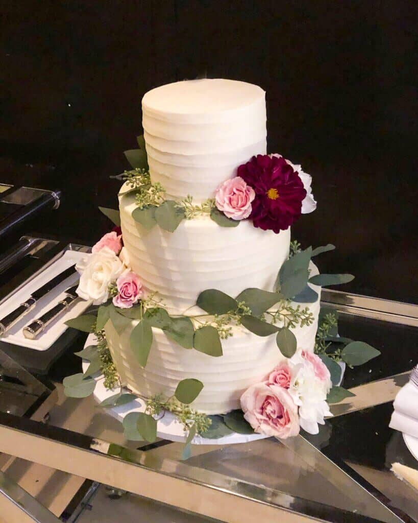 photo of finished wedding cake decorated with fresh flowers and greenery