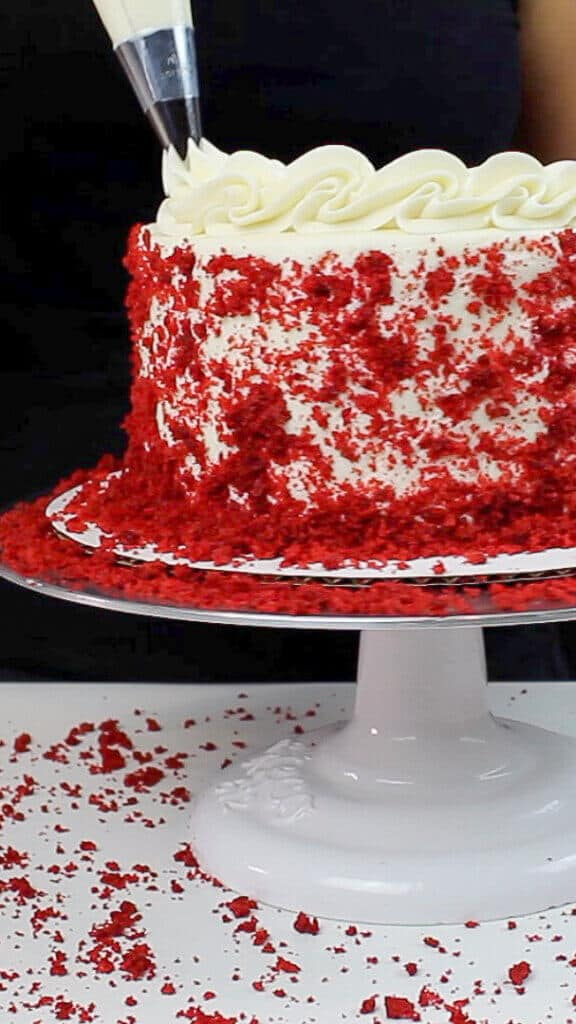 image of border being piped on red velvet layer cake