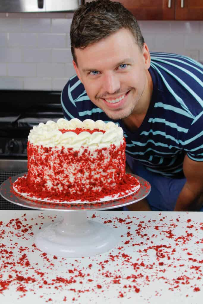 image of happy husband with red velvet layer cake