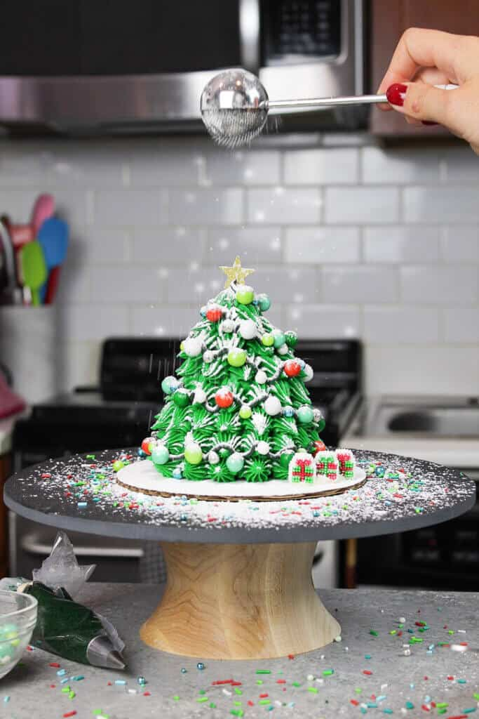 image of adding powdered sugar snow to christmas tree cake