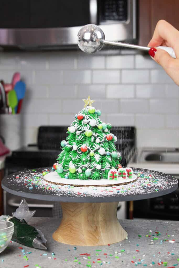image of small christmas tree cake being dusted with powdered sugar