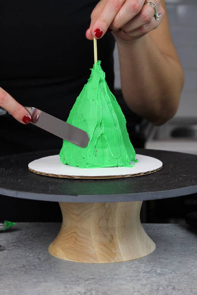 image of crumb coat being added to stacked cupcakes to make a mini christmas tree
