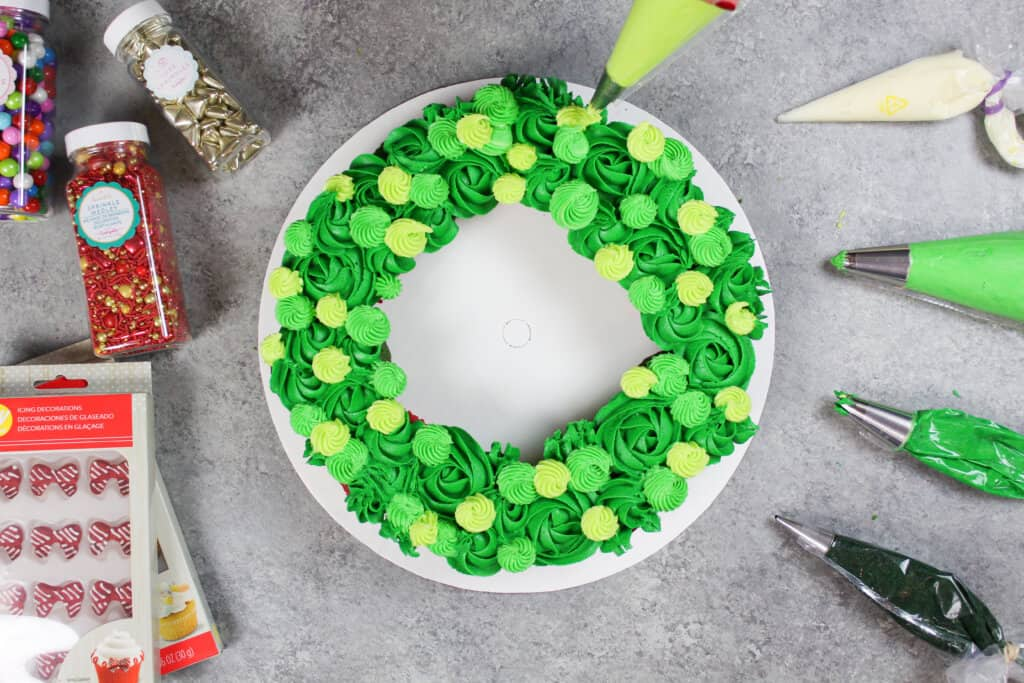 image of piping green buttercream frosting onto wreath cucpakes