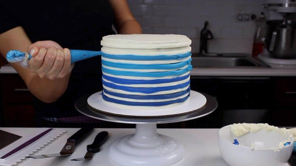 image of colorful frosting being piped onto buttercream cake