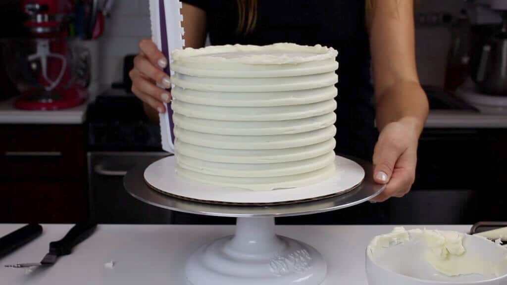 image of icing comb being used to create grooves for a striped buttercream cake