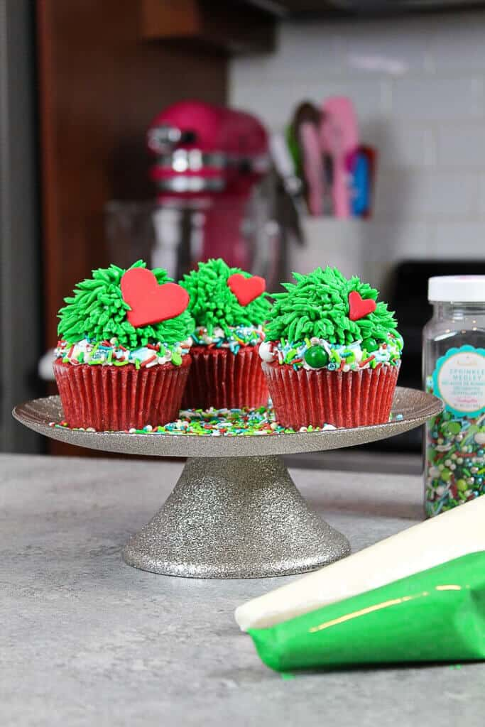 image of piping green buttercream fur onto a grinch cupcake