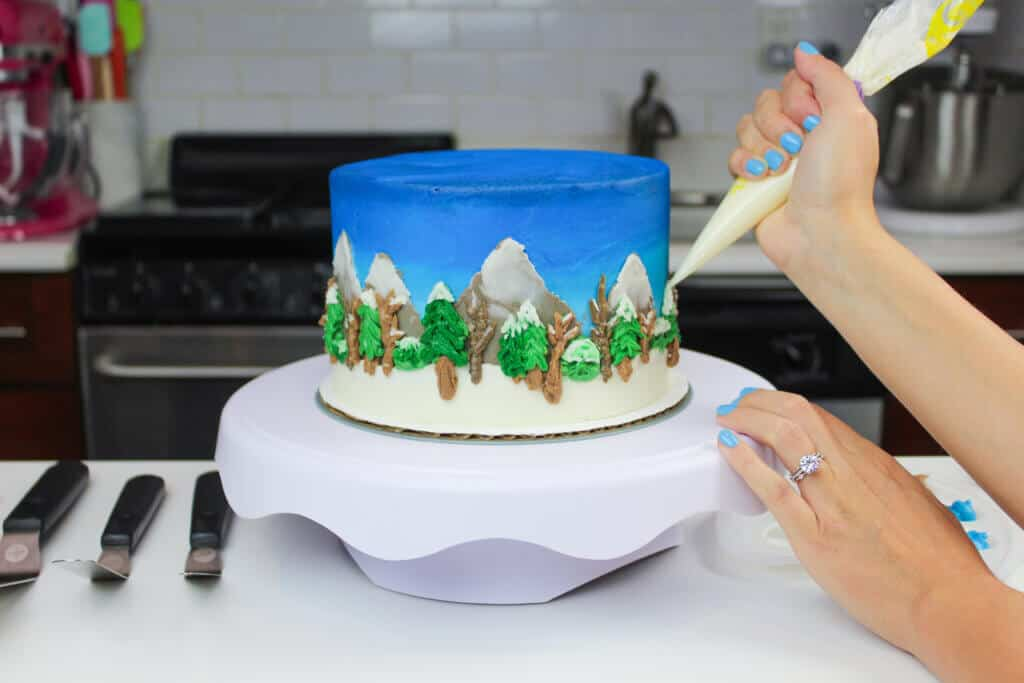 image of american buttercream being piped onto a detailed winter wonderland cake