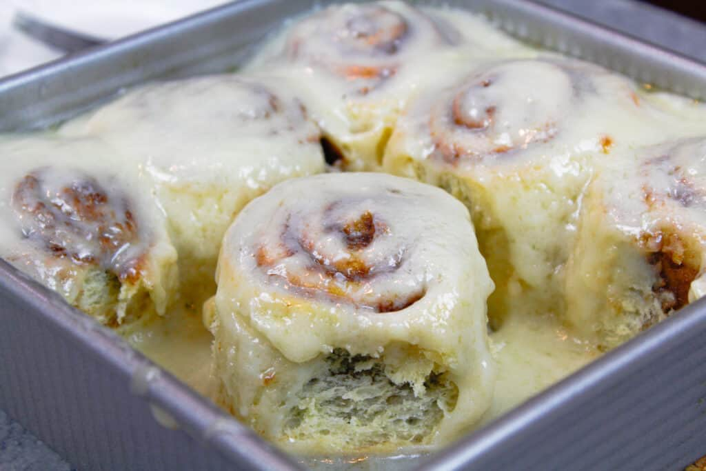 image of quick yeast cinnamon rolls glazed in a pan and ready to be eaten.