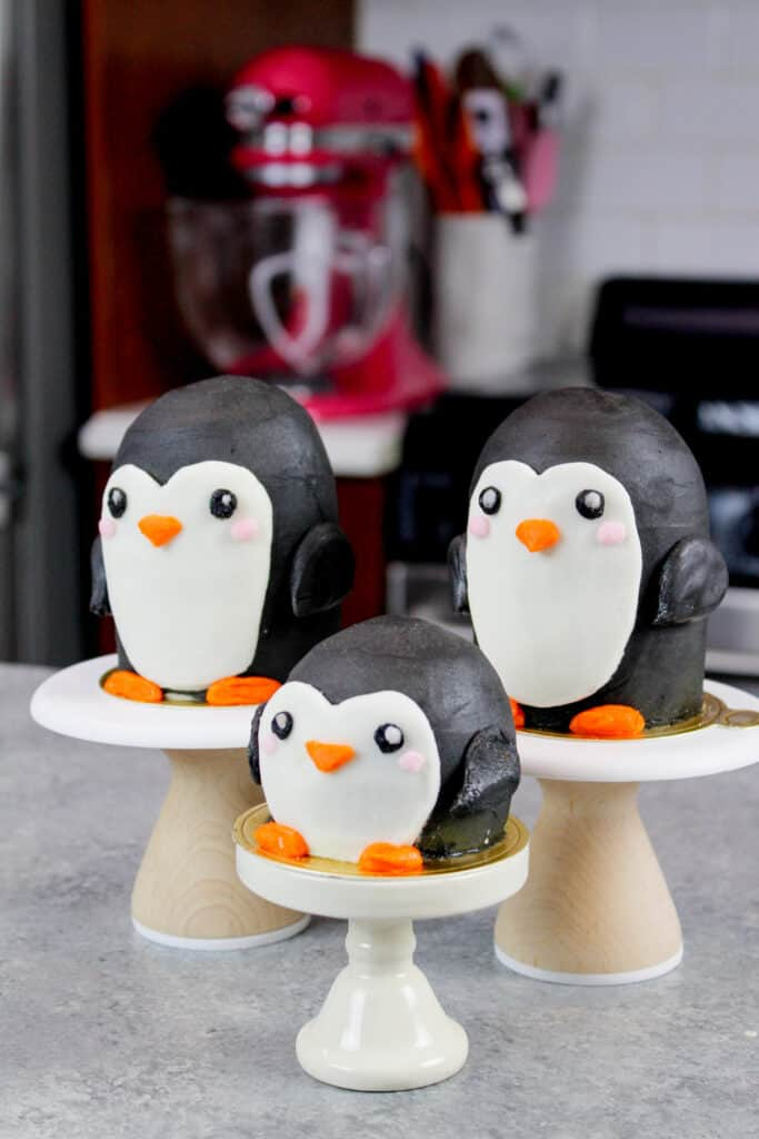 image of penguin cupcakes on mini pedestals, positioned to look like a little penguin family