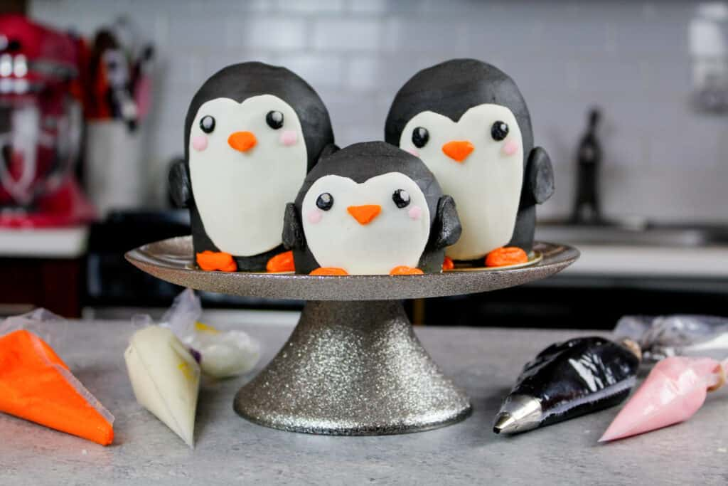 image of penguin cupcakes on cake stand with frosting bags around them