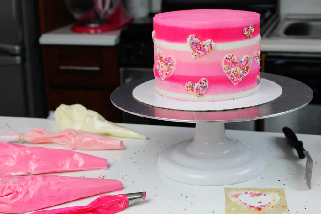image of pink valentine's day cake made with funfetti cake layers and decorated with sprinkle hearts