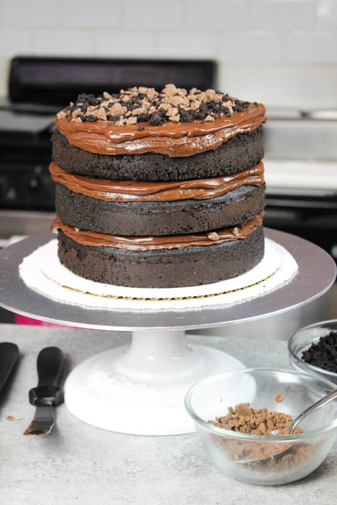 image of stacked chocolate cake layers with chocolate ganache frosting and pudding filling
