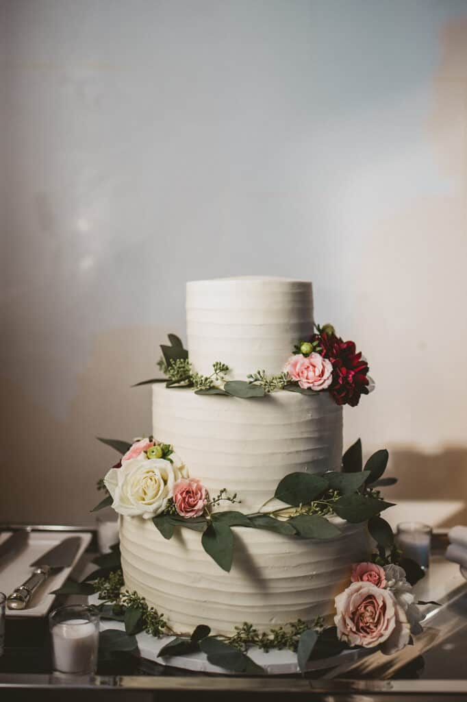 image of a simple rustic wedding cake decorated with fresh flowers