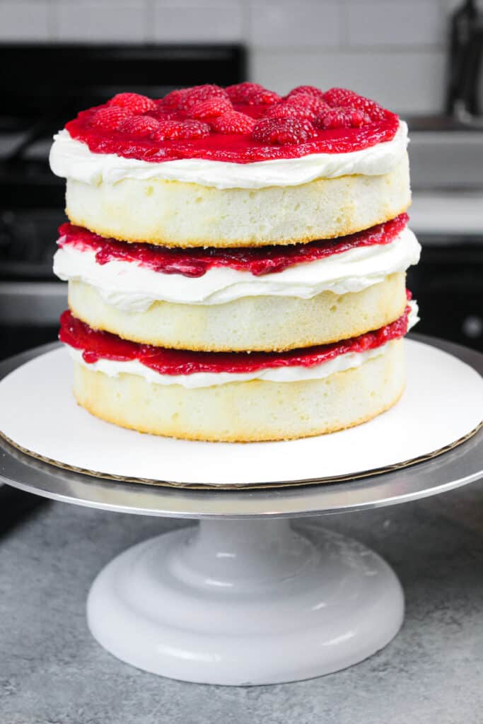 image of fluffy and soft white cake layers filled with white chocolate buttercream and a raspberry filling