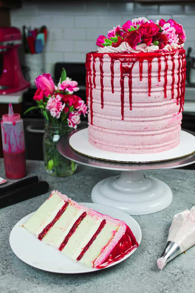 image of raspberry white chocolate cake decorated with fresh raspberries, flowers, and a white chocolate drip with slice in front