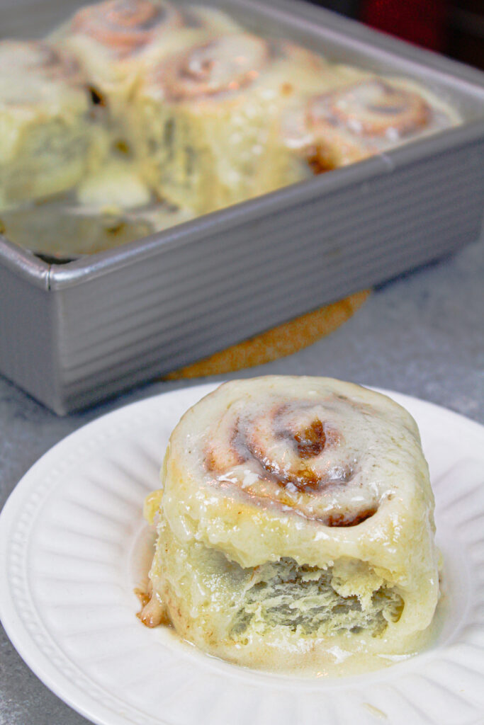 image of cinnamon roll on a plate, fluffy and soft with a gooey center, ready to be eaten