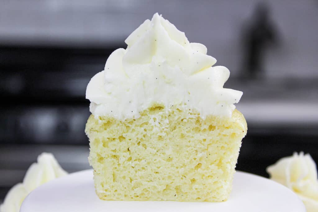 image of a gluten free vanilla cupcake cut in half, to show how moist and fluffy the cupcake is