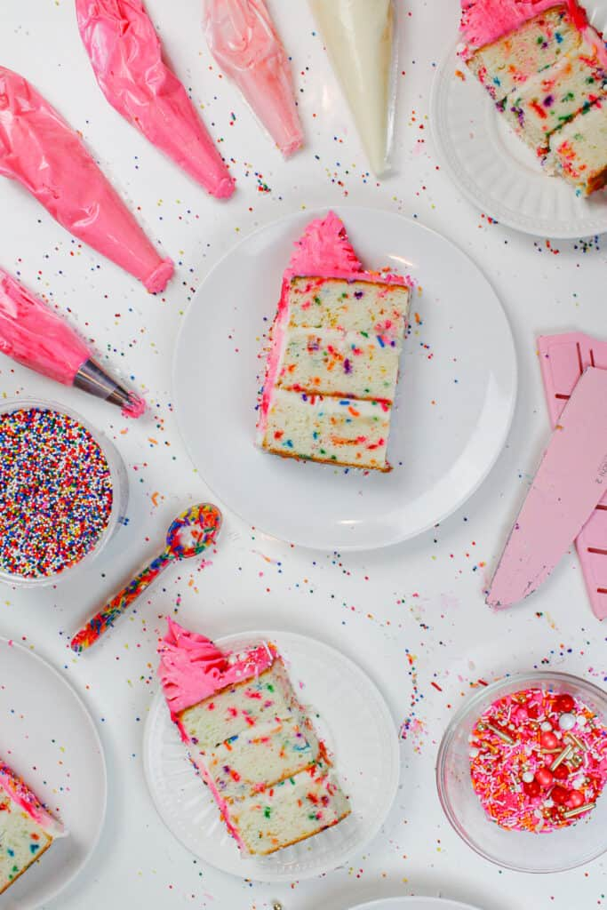 image of funfetti cake slices, cut and surrounded by pink frosting and rainbow sprinkles