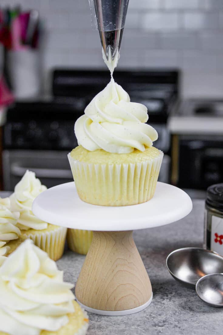image of gluten free vanilla cupcake being frosted with vanilla bean buttercream