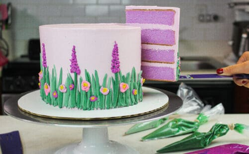 image of golden lavender cake cut with slice hovering in the air to show pretty and moist purple cake layers