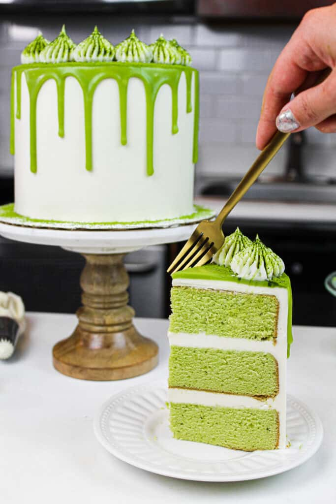 image of matcha cake slice on a plate with pretty matcha drip cake in background