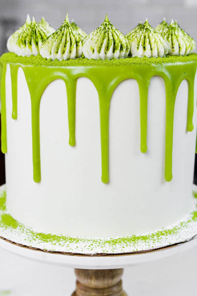 close up photo of a matcha cake decorated with white chocolate matcha ganache drips