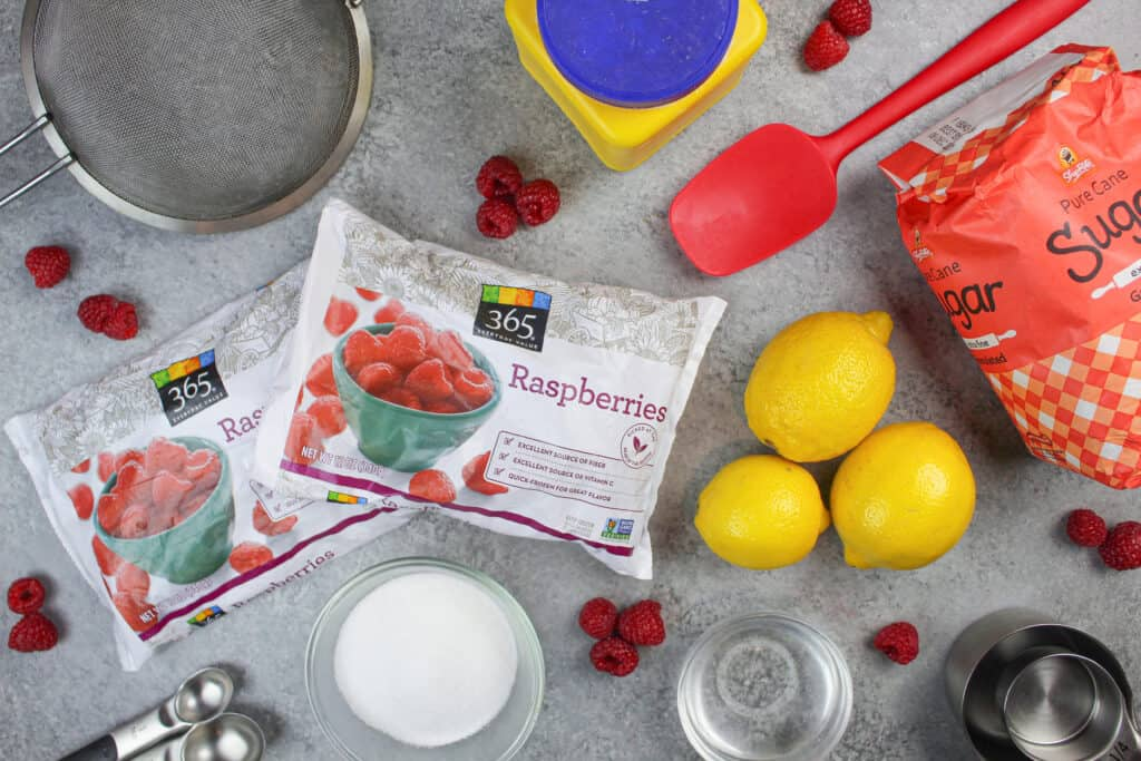 image of the ingredients used in this raspberry cake filling including frozen raspberries, sugar, and lemon juice