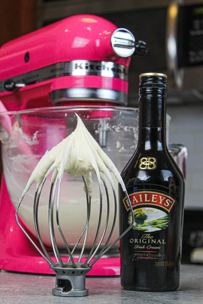 image of baileys frosting on whisk attachment resting on counter to show it's stiff enough to pipe with