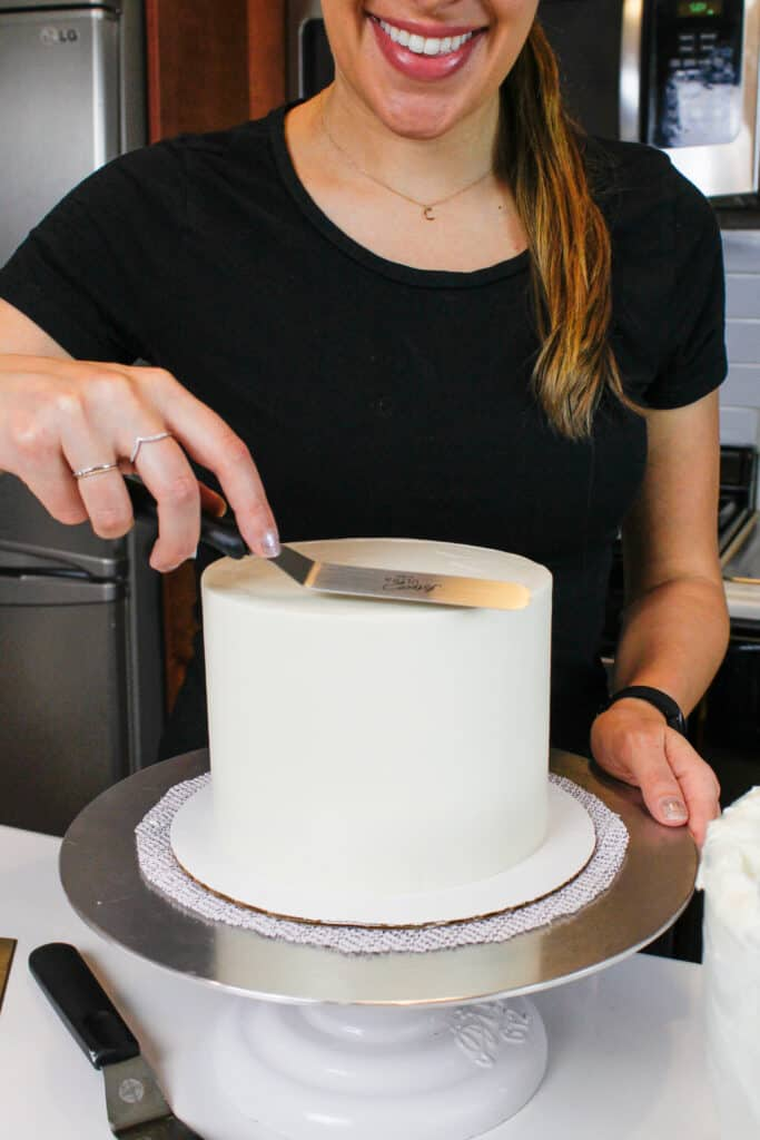 image of chelsey white of chelsweets smoothing frosting onto a cake