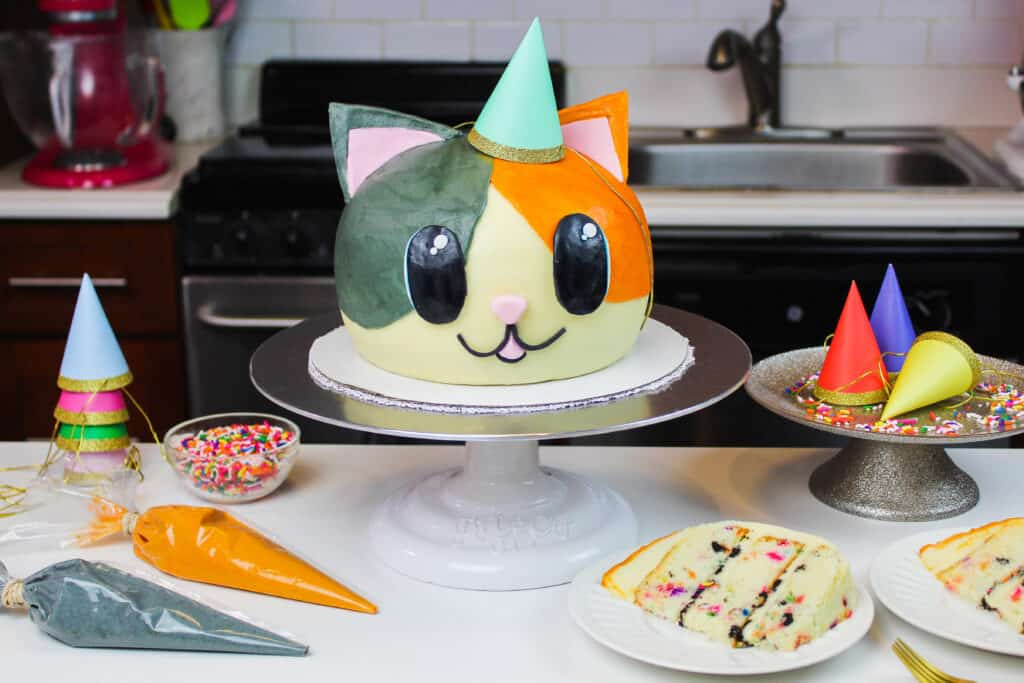 image of cat cake made by chelsweets with cute party hat on