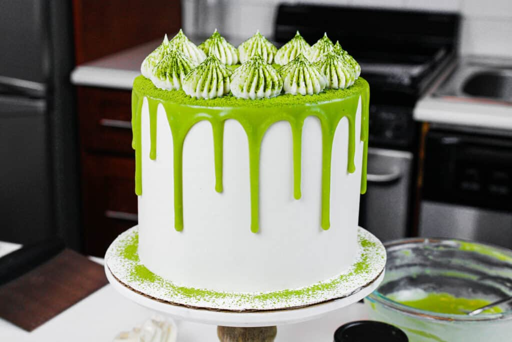 image of a matcha cake with fluffy buttercream frosting dusted in matcha powder
