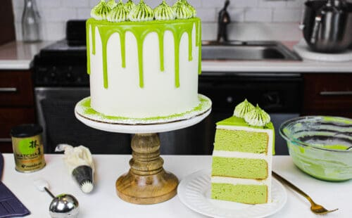 image of a matcha cake, with a slice placed on a plate to show how fluffy and delicious this matcha cake recipe is
