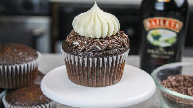 photo of a baileys chocolate cupcake on a small cupcake stand, decorated with chocolate sprinkles