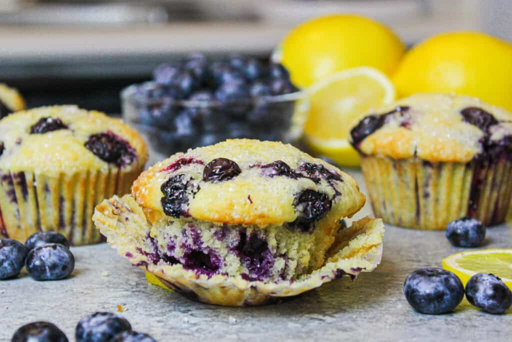 image of blueberry muffin surrounded by other muffins and fresh blueberries